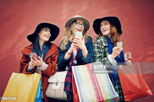 Girlfriends are texting with a shopping bags at the front of a red wall