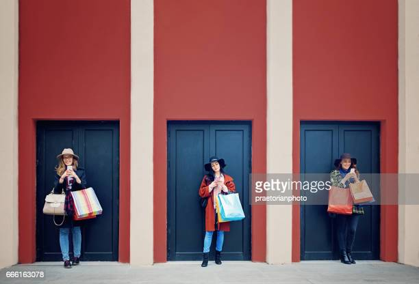 Girlfriends are texting with a shopping bags at the front of three doors