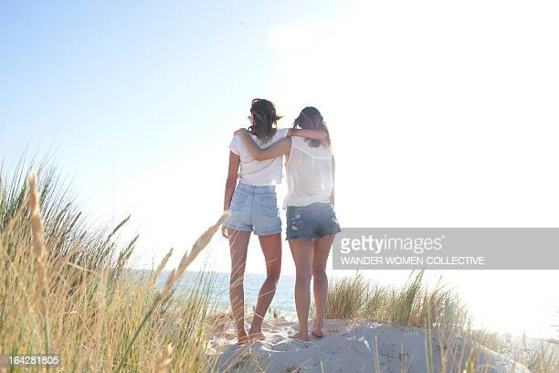 Girlfriends arm in arm on Australian beach