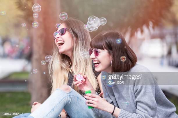 Girlfriends blowing soap bubbles