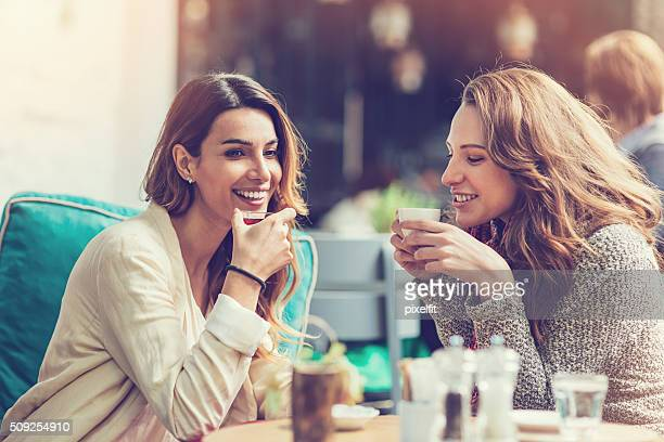 girlfriends chatting and having coffee - girlfriend stock photos and pictures