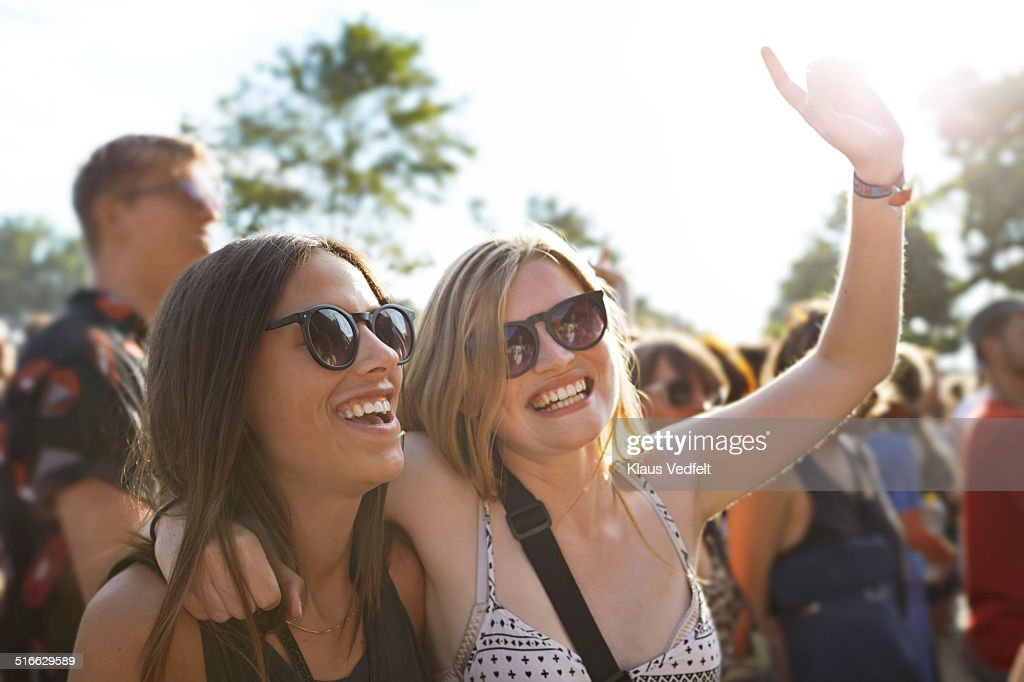 2 girlfriends cheering at concert outside : Stock Photo