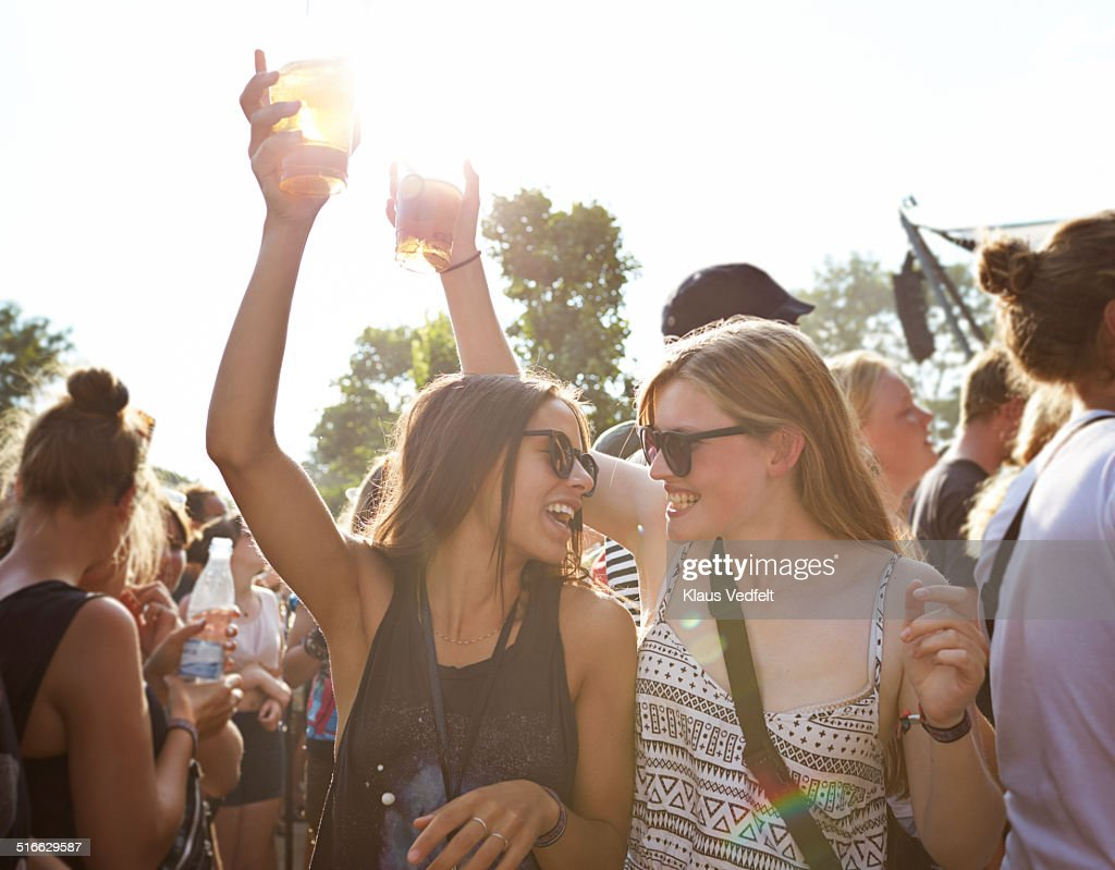 Girlfriends cheering with beer at concert outside : Stock Photo