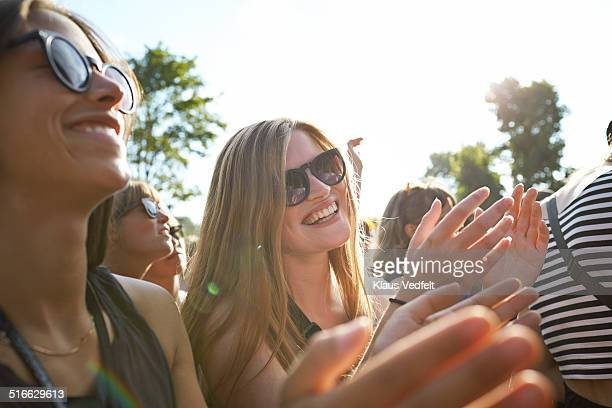 2 girlfriends clapping at concert outside