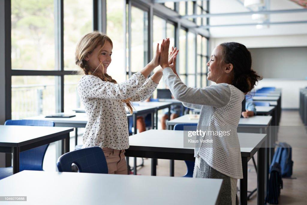 Girlfriends doing clapping game in classroom : Foto de stock