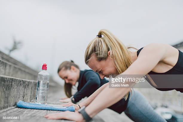 girlfriends doing push-ups together - outdoors stock-fotos und bilder