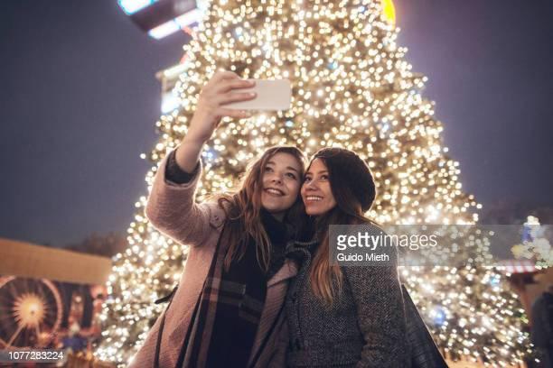 Girlfriends doing selfie in front of christmas tree.