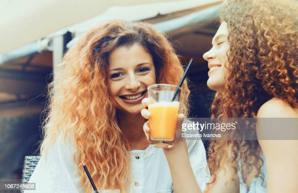 Girlfriends drinking orange juice and laughing