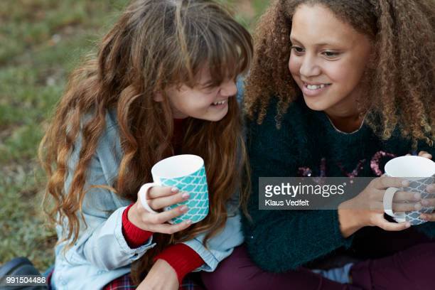 Girlfriends drinking tea out side and laughing