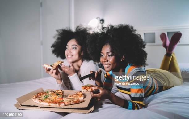 vriendinnen die pizza in bed eten en tv letten - onderdeel van een serie stockfoto's en -beelden
