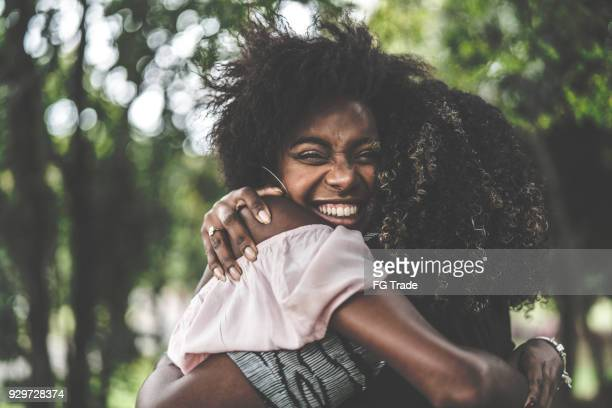 girlfriends embracing - istantanea foto e immagini stock