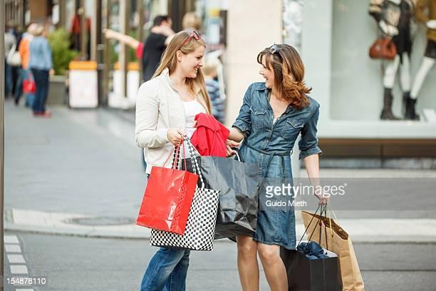 Girlfriends enjoy shopping in city.