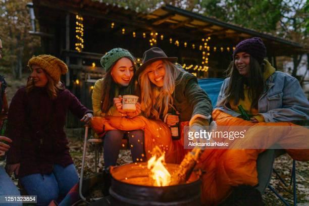 キャンプファイヤーで楽しむガールフレンド - キャンプファイヤー ストックフォトと画像