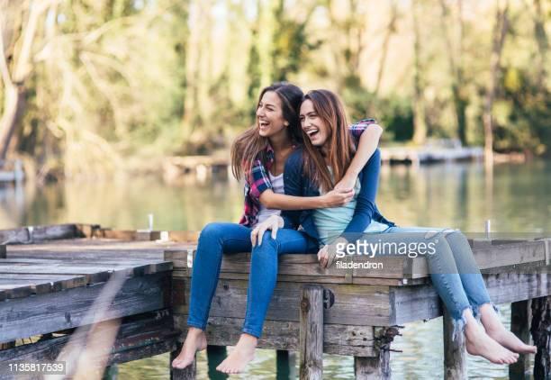girlfriends enjoying time together near the river - sorella foto e immagini stock