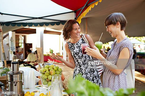 Girlfriends having healthy juice at food market
