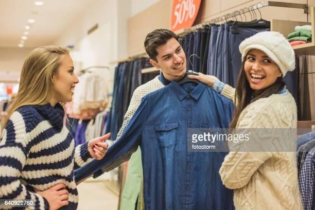 vriendinnen helpen jonge man om te winkelen voor shirt - the past stockfoto's en -beelden
