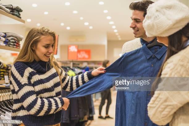 Girlfriends helping young man to shop for shirt