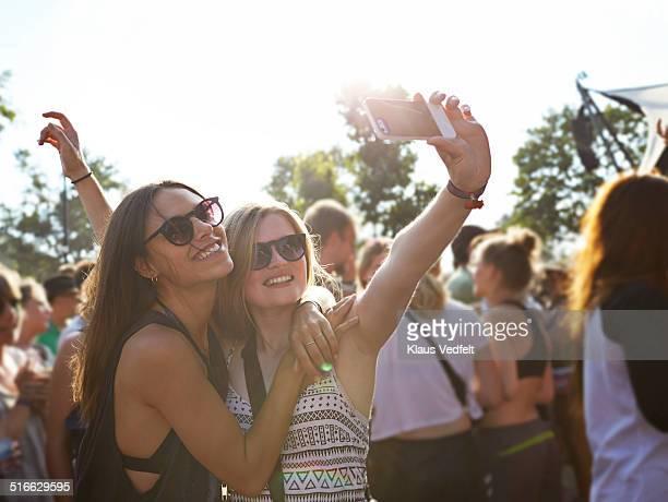 Girlfriends hugging & making selfie at concert