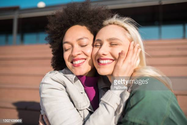 girlfriends hugging - international womens day stock pictures, royalty-free photos & images