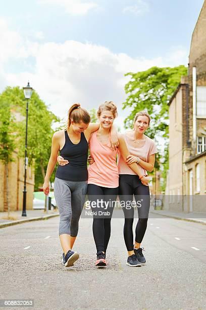 Girlfriends in sports clothes walking down street