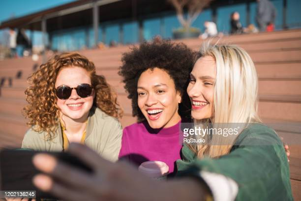 girlfriends laughing and taking a selfie - international womens day stock pictures, royalty-free photos & images