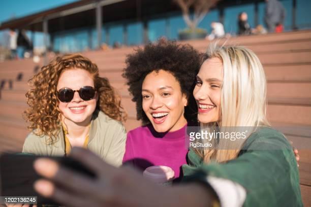 freundinnen lachen und machen ein selfie - womens day stock-fotos und bilder