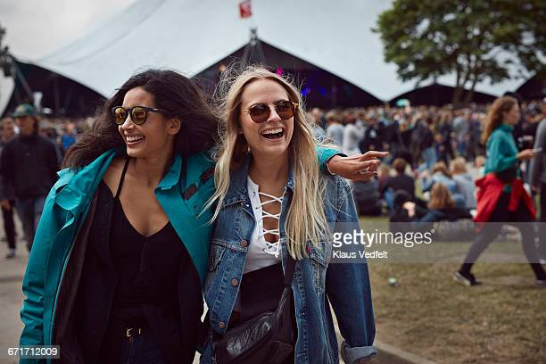 Girlfriends laughing together at outside festival