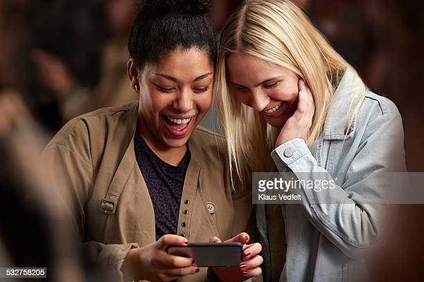 Girlfriends looking at phone together among crowd