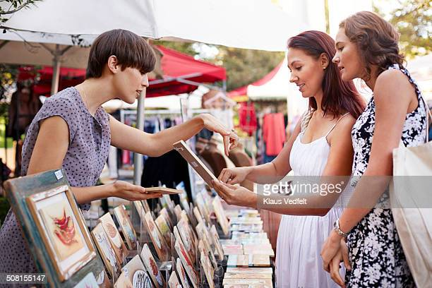 Girlfriends looking at small paintings at market