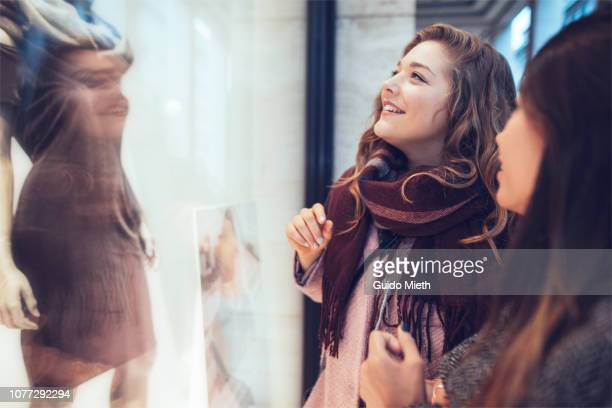 girlfriends looking into shopping window. - winkelen stockfoto's en -beelden