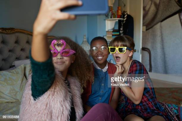 Girlfriends making selfie and wearing weird, funny glasses
