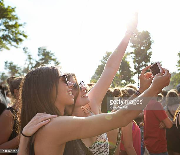 Girlfriends making selfie at concert, outside