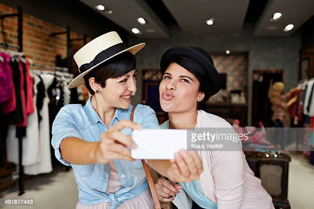 Girlfriends making selfie in fashion shop