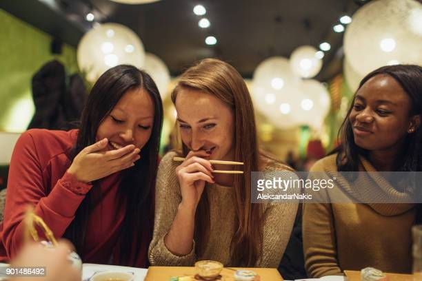 girlfriends on the night out - sushi restaurant stock photos and pictures