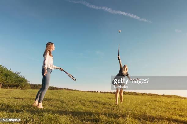 copines jouer au badminton sur terrain gazonné pendant le coucher du soleil - volant de badminton photos et images de collection