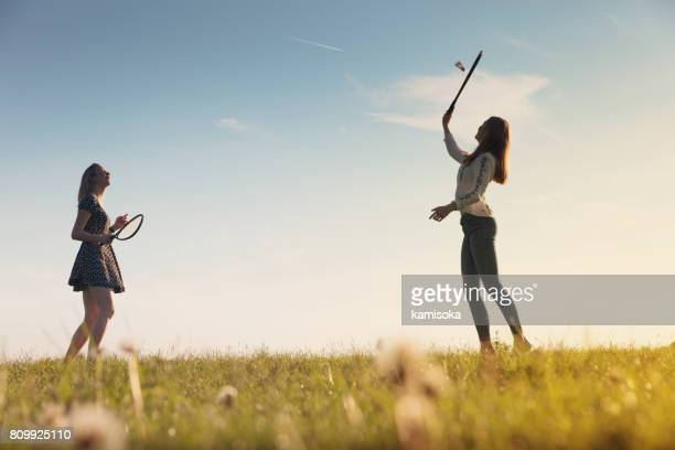 Girlfriends playing badminton on grassy field during sunset