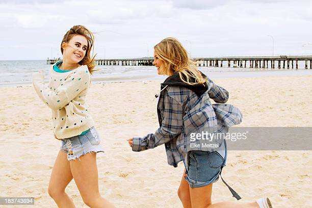girlfriends playing chasing game on the beach - 追いかける ストックフォトと画像