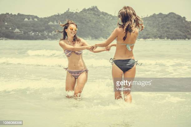 Girlfriends playing in waves on beach