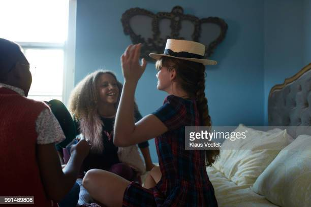 Girlfriends playing with hats at home