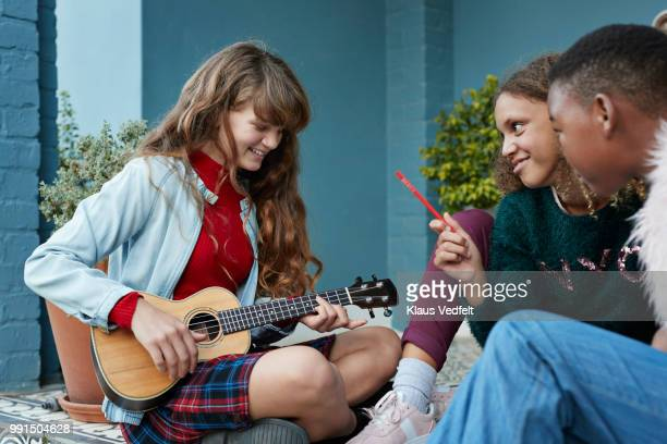 Girlfriends practicing ukulele together on the porch