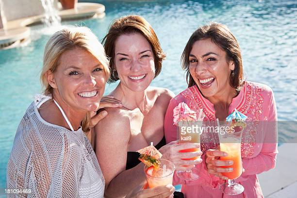 Girlfriends relaxing by pool with drinks