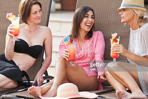 girlfriends relaxing by pool with drinks - poolside stock pictures, royalty-free photos & images