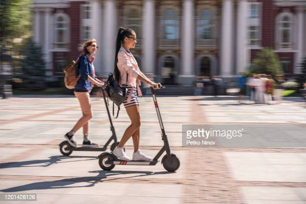 girlfriends riding e-scooters in the city - electric scooter stock pictures, royalty-free photos & images