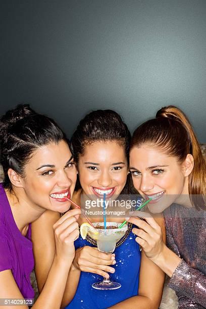 Girlfriends Sharing Cocktail Through Straw In Nightclub