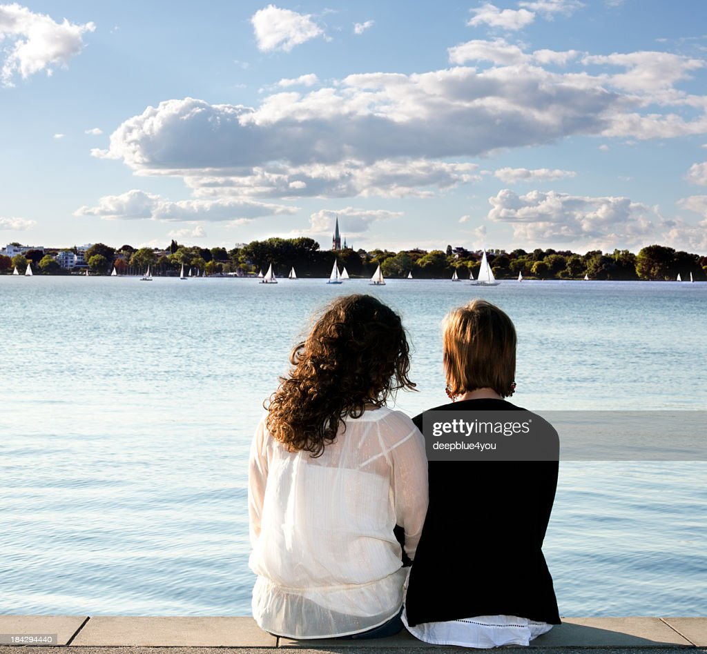 Girlfriends sitting on pier looking out over water : Stock Photo