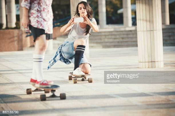 girlfriends skateboarding and photographing with mobile phone - influencer stock photos and pictures