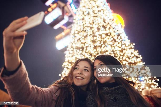 Girlfriends taking a selfie in front of christmas tree.
