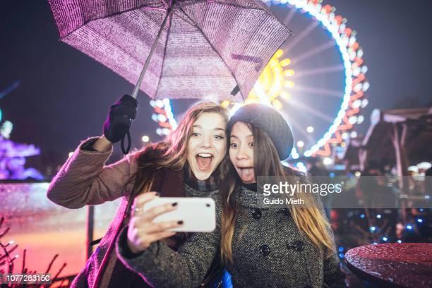 Girlfriends taking a selfie on christmas market.