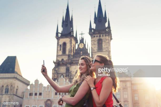 girlfriends taking selfies in front of tyn church in prague - prague stock pictures, royalty-free photos & images