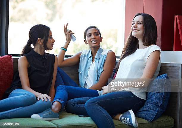 girlfriends talking & laughing at school - three people stock pictures, royalty-free photos & images